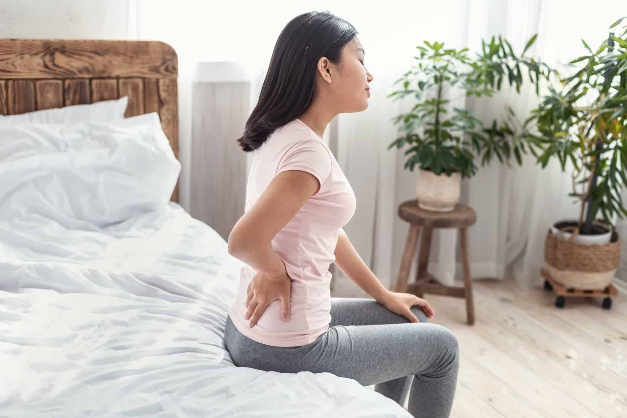 Asian Lady Suffering From Pain In Back Sitting On Bed