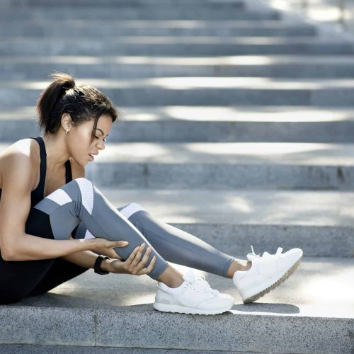 African woman in sport clothes sitting on stairs, massaging ancle